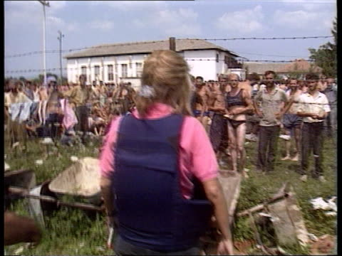 prison camps: omarska / trnopolje:; naf: bosnia-herzegovina: trnopolje camp: ext gv prisoners standing behind wire fence track forward prisoners... - bosnian war stock videos & royalty-free footage