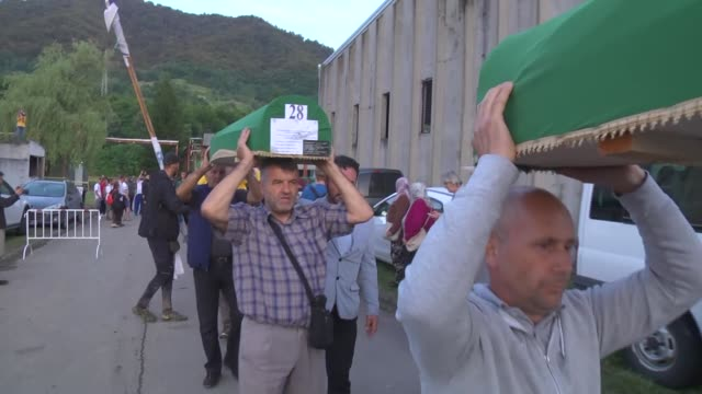 Bosnians carry the coffins of recently identified remains of 33 victims of Srebrenica Genocide at battery factory which was used as a military base...