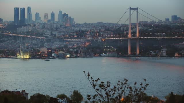 vídeos de stock e filmes b-roll de t/l ws bosphorus bridge and skyline, day to night transition, istanbul, turkey - estreito descrição física