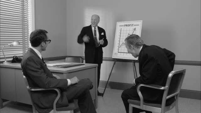 b/w ms boss giving presentation about increased profits to two businessmen/ boss getting excited  putting arb/w ms around men/ new york city - svartvit bild bildbanksvideor och videomaterial från bakom kulisserna