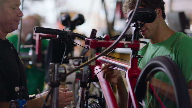 Boss inspects brake cables on bicycle and instructs young mechanic working in bike shop