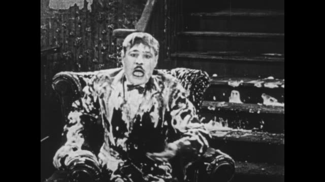 1925 Boss (Oliver Hardy) shouts as flustered wallpaper helper makes a mess before wiping hands on man's beard and swinging ladder around