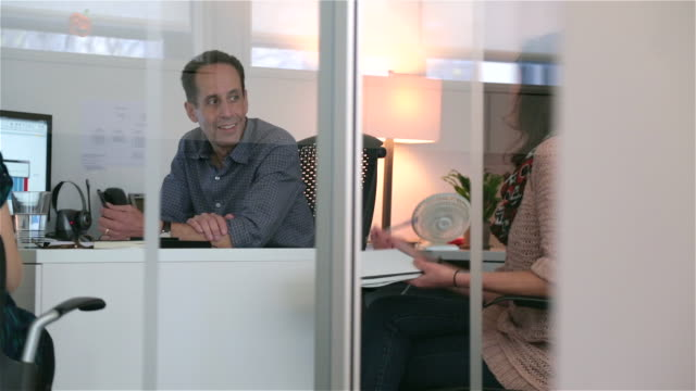 Boss twirls pen, listens to businesswoman in private corporate office meeting (dolly shot)