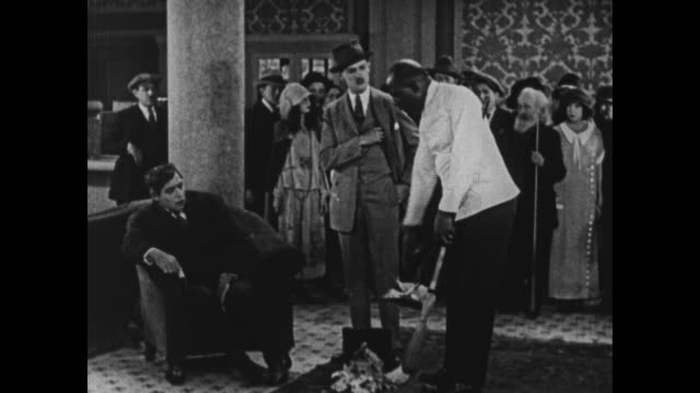1924 bossy man spills trash in hotel lobby but sends porter away as he tries to clean it up - 1924年点の映像素材/bロール