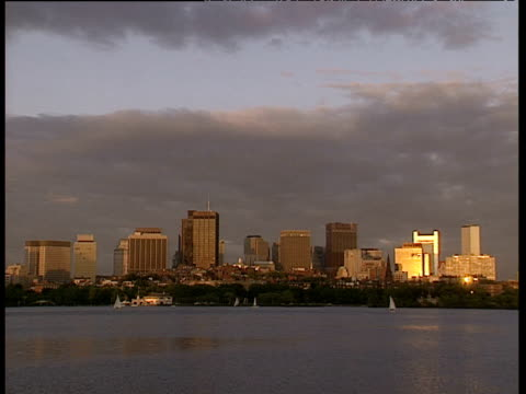 boston skyline across rippling water with boats in distance sun reflects on buildings to right of picture stormy clouds overhead - boston massachusetts stock videos & royalty-free footage