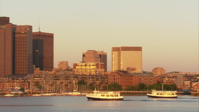 ws boston skyline with custom house clock tower seen across boston harbor with boats at sunset / boston, massachusetts, usa - custom house tower stock videos & royalty-free footage