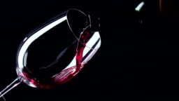 Bottle and glass with red luxury wine, black, closeup, slowmotion