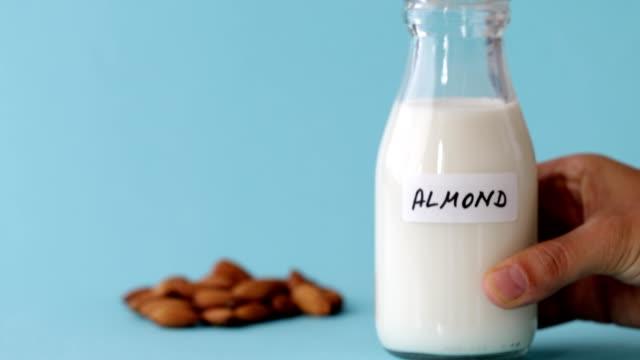 a bottle of almond milk on blue background - milk jug stock videos & royalty-free footage