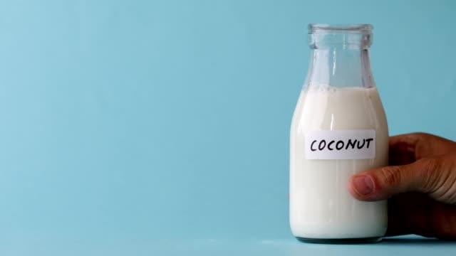 a bottle of coconut milk on blue background - milk jug stock videos & royalty-free footage
