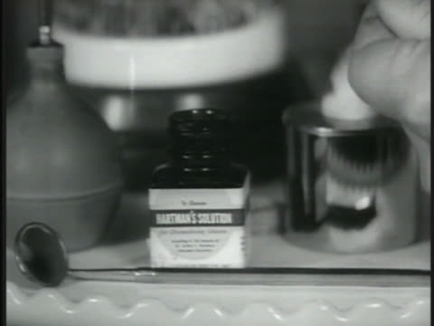 vidéos et rushes de bottle of hartman's solution sitting on counter, male hand holding tweezers w/ swab dipping into, out of bottle. - pince chirurgicale
