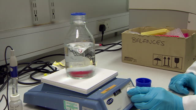 a bottle of liquid is placed on a magnetic agitator in a dna laboratory. - genetic research stock videos & royalty-free footage
