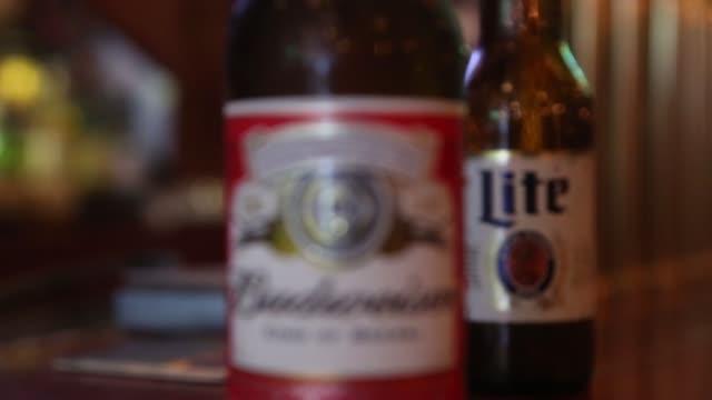 a bottle of miller high life beer sits at a bar on october 9 2015 in new york city budweiser's parent company ab inbev is attempting to buy sabmiller - anheuser busch inbev stock-videos und b-roll-filmmaterial