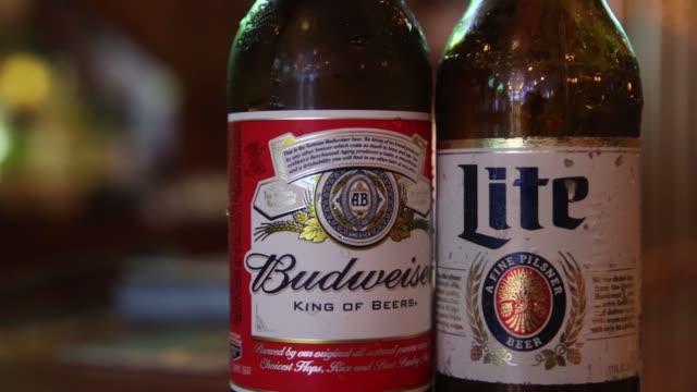 vídeos y material grabado en eventos de stock de a bottle of miller high life beer sits at a bar on october 9 2015 in new york city budweiser's parent company ab inbev is attempting to buy sabmiller - anheuser busch inbev