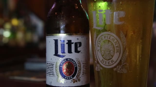 a bottle of miller high life beer sits at a bar on october 9 2015 in new york city budweiser's parent company ab inbev is attempting to buy sabmiller - anheuser busch inbev stock videos and b-roll footage