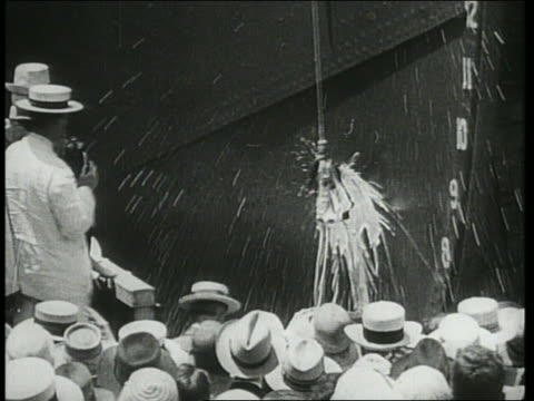 b/w 1942 bottle on rope hitting bow of ship in christening as crowd watches / we do it because... - stapellauf stock-videos und b-roll-filmmaterial