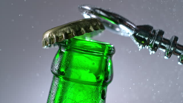 slo mo ld bottle opener opening the bottle cap of a green bottle - cap stock videos & royalty-free footage