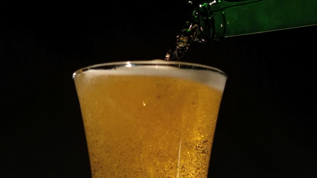bottle pouring beer into glass - empty beer glass stock videos and b-roll footage