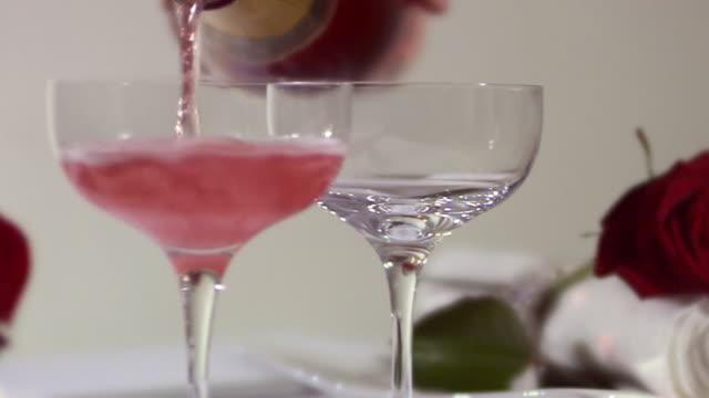 A bottle pouring wine into two glasses Sweden.