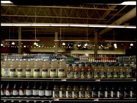 Bottled goods sodas vitamin water on top of shelves in grocery store aisles Supermarket grocery shopping aisle bottles drinks beverages