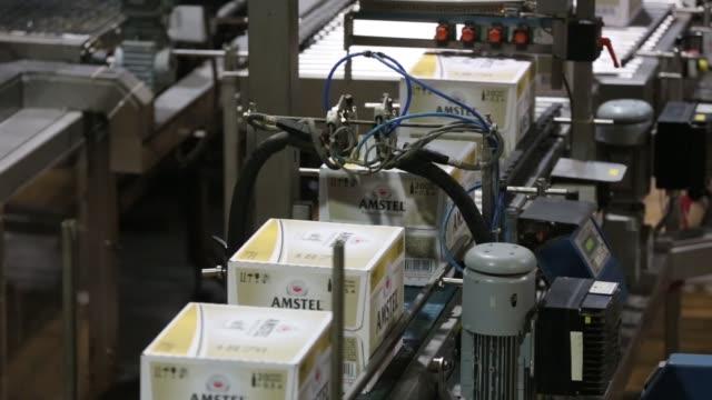 bottles and crates of heineken beer and amstel pilsner beer move along the production line at the heineken nv brewery in saint petersburg russia on... - pilsner stock videos & royalty-free footage