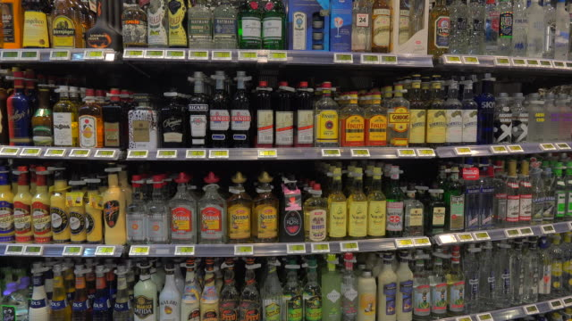bottles arranged in liquor store - alkoholisches getränk stock-videos und b-roll-filmmaterial