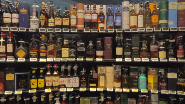 bottles arranged in liquor store - scaffale video stock e b–roll
