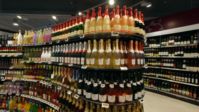 bottles arranged in liquor store - bottiglia video stock e b–roll