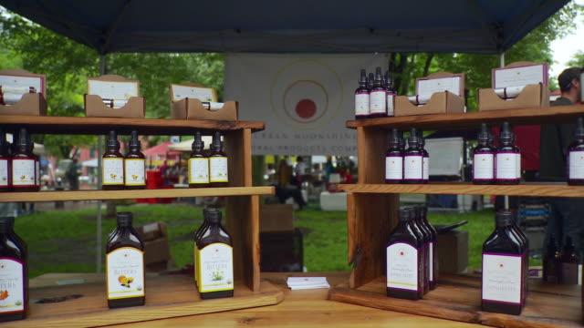 ms pan bottles arranged on shelf and man working in background / burlington, vermont, usa  - burlington vermont bildbanksvideor och videomaterial från bakom kulisserna