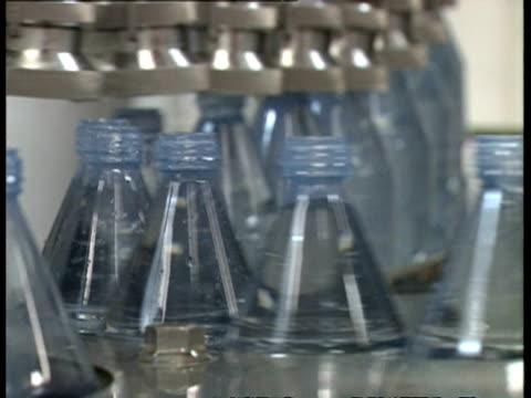 CU Bottles being filled with water, on conveyor belt in water bottling factory