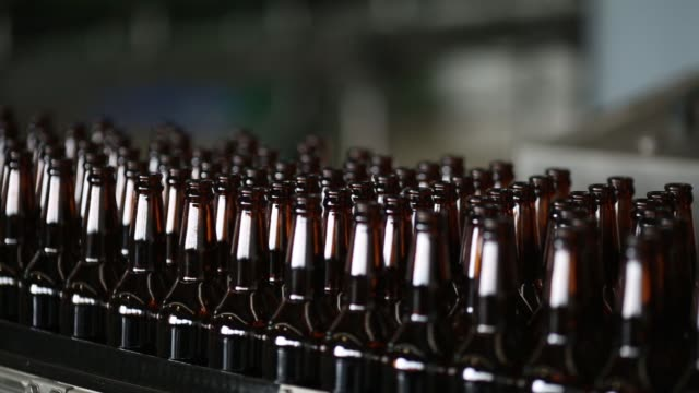 bottles enter a cleaning machine on the bottling line at the carlsberg a/s plant in nyaung inn village bago myanmar on wednesday oct 7 uncapped... - beer bottle stock videos & royalty-free footage