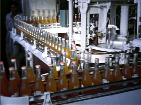 vídeos de stock, filmes e b-roll de 1951 bottles filled with orange liquid moving slowly on diverging conveyor belts - bebida não alcoólica