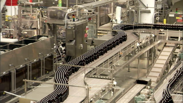bottles move along a conveyor in a bottling plant. - bottling plant stock videos & royalty-free footage