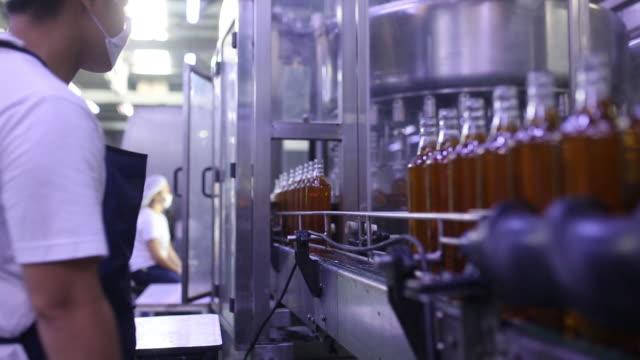 bottles of alcohol moving on conveyor belt at destileria limtuaco factory manila national capital region philippines on tuesday july 16 2019 - capital region stock videos & royalty-free footage