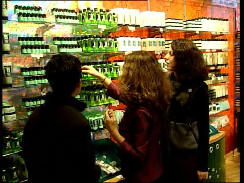 Bottles of Body Shop Tea Tree Oil Facial Wash CS Bottles of Body Shop Hydrating Moisture Lotion CS Body Shop products on shelf Customers in Body Shop...