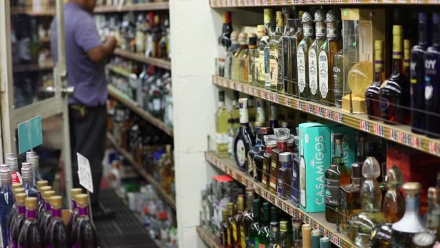 bottles of casamigos blanco and anejo tequilas are displayed on a shelf for sale at a liquor store in los angeles california us on thursday june 22... - liquor store stock videos and b-roll footage