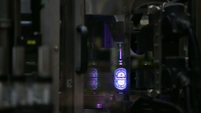bottles of heineken beer pass through a labeling machine at the heineken nv brewery in den bosch netherlands on tuesday nov 19 heineken decals pass... - labelling stock videos & royalty-free footage