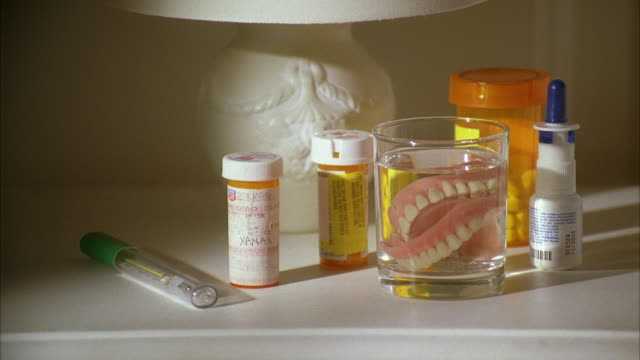 stockvideo's en b-roll-footage met ms bottles of prescription medicine and false teeth in glass on night table - middelgrote groep dingen