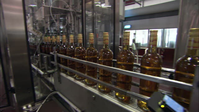 bottles of rum travel along a conveyor belt. - rum stock videos and b-roll footage