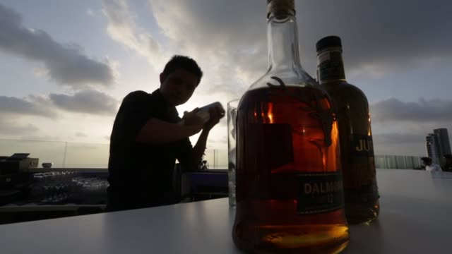 bottles of united spirits ltd's jura left and dalmore scotch whiskies sit on a bar counter at the aer rooftop bar at the four seasons hotel in the... - plc stock videos & royalty-free footage
