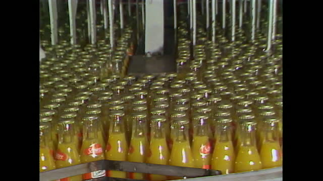 bottles of unsweetened orange juice in schweppes factory; 1984 - carbonated stock videos & royalty-free footage