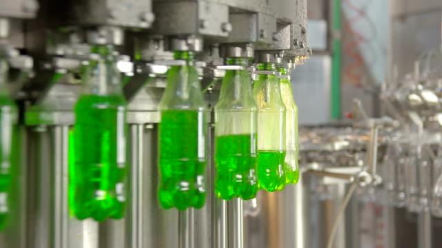 bottling of lemonade in plastic bottles. lemonade bottle conveyor industry - bottling plant stock videos and b-roll footage