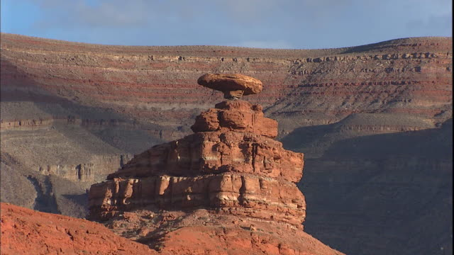 A boulder balances on top of a tall desert cliff.