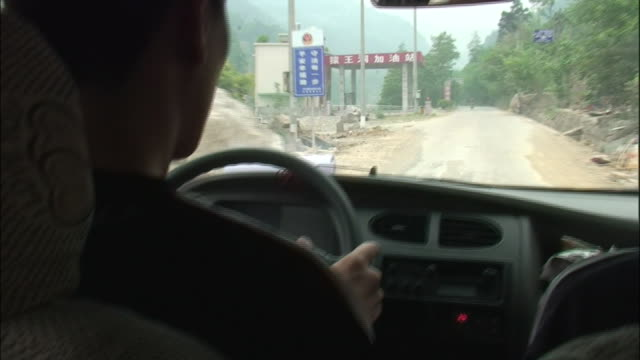 vidéos et rushes de a boulder crowds a mountain road from the point of view of a passing car following the sichuan earthquake - car point of view