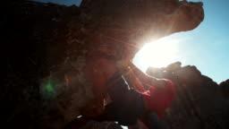 Bouldering rock climber hanging beneath extreme overhang against blue sky