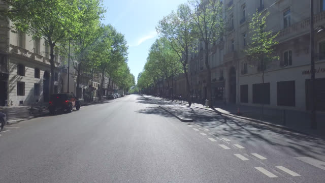 boulevard saintgermain with only four pedestrians and without traffic april 15 2020 in paris france the country is issuing fines for people caught... - four people stock videos & royalty-free footage