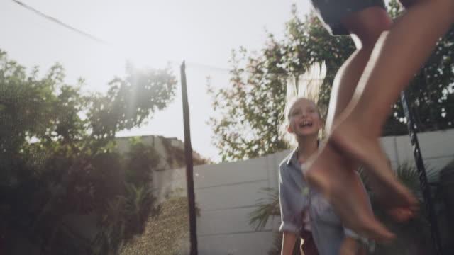 彼らの裏庭で跳ね回る - トランポリン点の映像素材/bロール