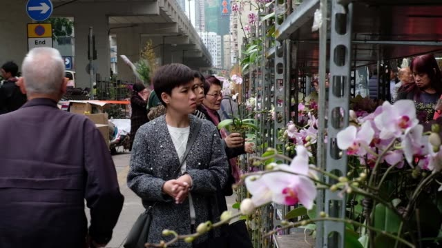 Bouquets of roses rear stand outside a flower shop as shoppers walk past at a flower market ahead of Lunar New Year in the Mong Kok district of Hong...