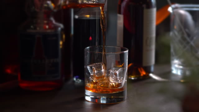 vidéos et rushes de bourbon poured over ice in rocks glass - whisky