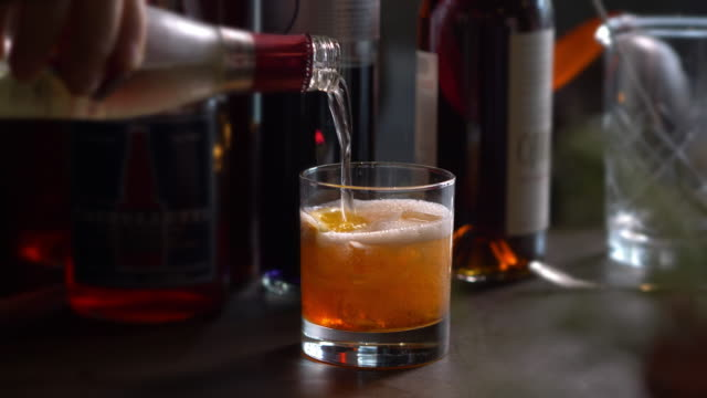 bourbon poured over ice in rocks glass - frothy drink stock videos and b-roll footage