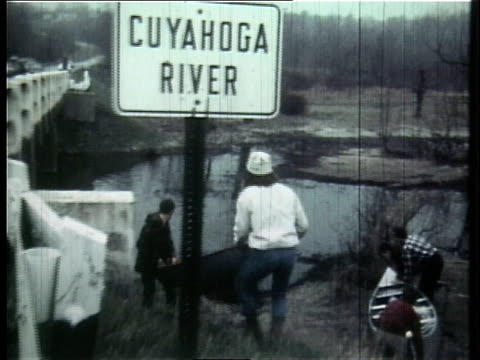 1966 montage bouters loading canoes and paddling the river / ohio, united states - fiume cuyahoga video stock e b–roll